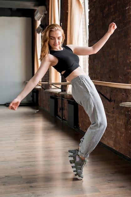 Blonde junge frau, die auf seinem fuß im tanzstudio balanciert Kostenlose Fotos