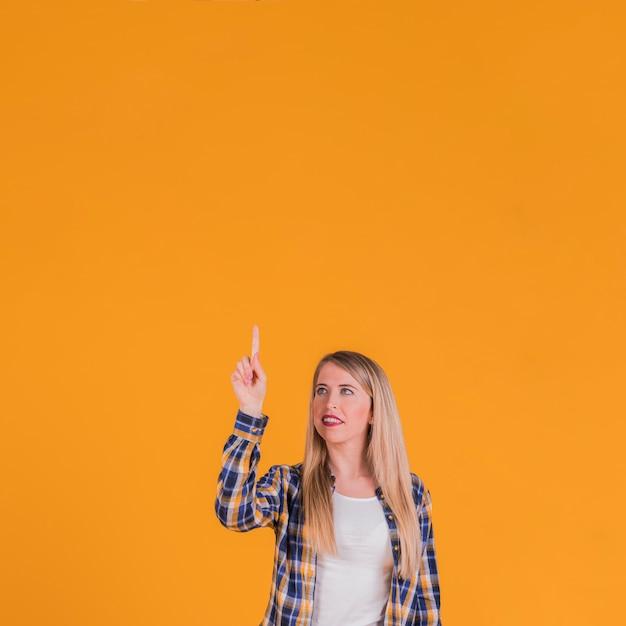 Blonde junge frau, die aufwärts ihren finger gegen einen orange hintergrund zeigt Kostenlose Fotos