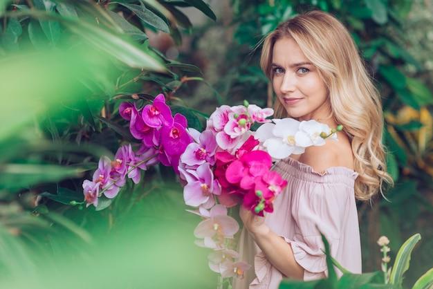 Blonde junge frau, die im garten hält orchidee steht Kostenlose Fotos