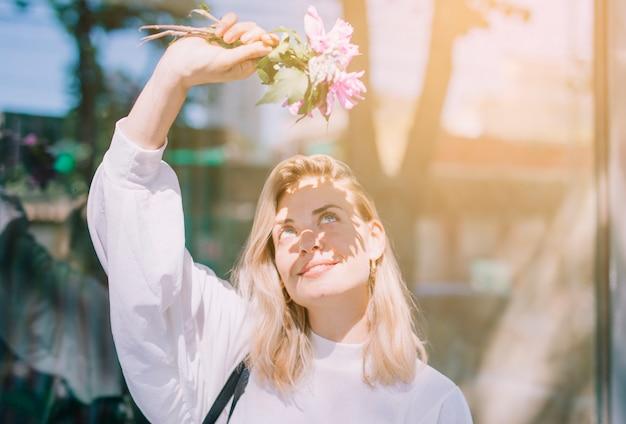 Blonde junge frau, die in der hand blumen hält, die ihre augen vom sonnenlicht abschirmen Kostenlose Fotos