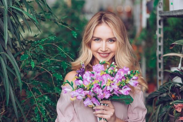 Blonde junge frau, die purpurroten blumenblumenstrauß in den händen hält Kostenlose Fotos