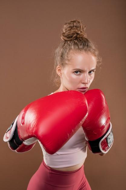 Blonde junge frau in aktivkleidung und roten boxhandschuhen Premium Fotos