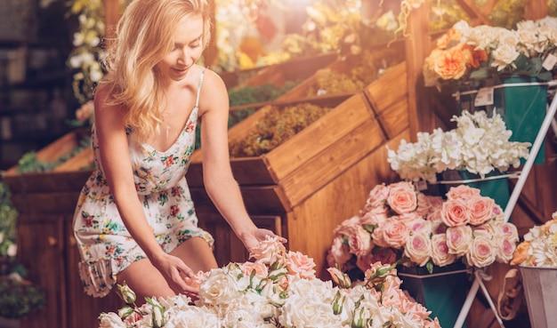 Blonde junge frau, welche die rosen im blumengeschäft berührt Kostenlose Fotos