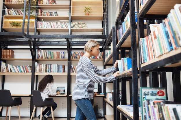 Blonde junge gutaussehende frau in gestreiftem hemd und jeans, die nach einem buch im regal in der bibliothek sucht und sich auf prüfungen in der universität vorbereitet Kostenlose Fotos