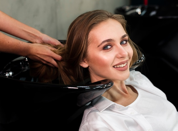 Blonde lächelnde frau, die haar gewaschen erhält Kostenlose Fotos