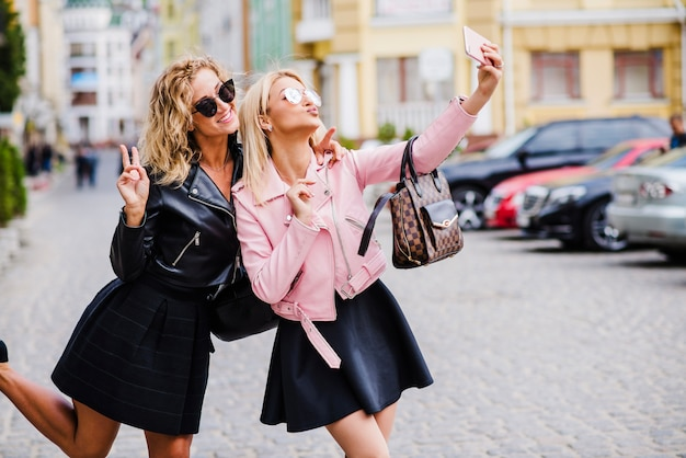 blonde mädchen stehen auf der straße machen selfie