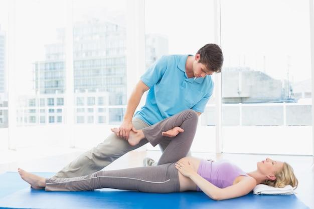 Blonde schwangere frau, die eine entspannende massage erhält Premium Fotos