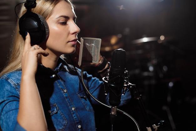 Blonde singende frau in einem aufnahmestudio Premium Fotos
