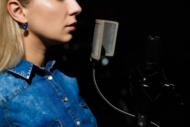 Blonde singende frau in einem tonstudio Premium Fotos