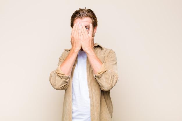 Blonder erwachsener mann, der gesicht mit händen bedeckt, mit überraschtem ausdruck zwischen den fingern späht und zur seite schaut Premium Fotos