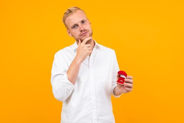 Blonder europäer macht einen vorschlag, der einen ring in einer box auf gelbem grund hält. Premium Fotos