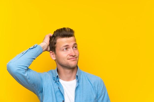 Blonder gutaussehender mann, der zweifel und mit verwirrtem gesichtsausdruck hat Premium Fotos