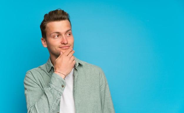 Blonder gutaussehender mann mit grünem hemd eine idee denkend Premium Fotos