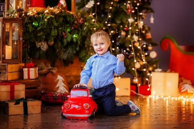 Blonder junge des babys nahe bei dem weihnachtsbaum Premium Fotos
