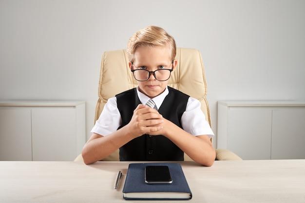 Blonder kaukasischer junge, der im büro sitzt und vortäuscht, leitprogramm zu sein Kostenlose Fotos