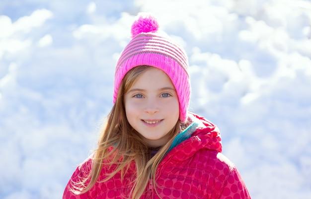 Blonder kindermädchen-winterhut im schneelächeln Premium Fotos
