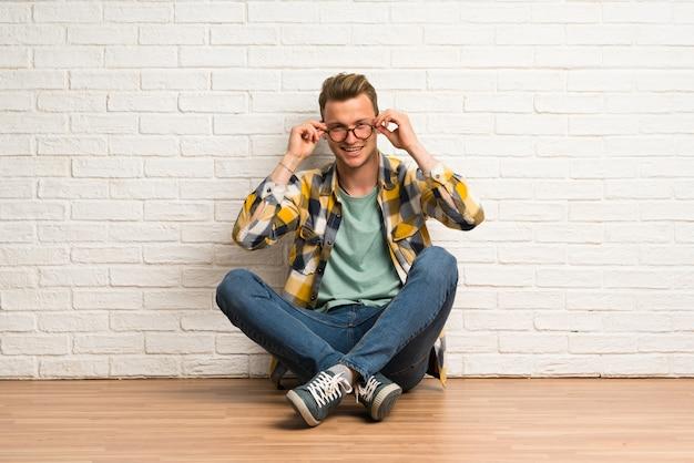 Blonder mann, der auf dem boden mit gläsern und überrascht sitzt Premium Fotos