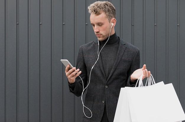 Blonder mann im schwarzen schauenden smartphone Kostenlose Fotos