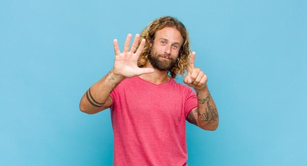 Blonder mann lächelt und sieht freundlich aus, zeigt nummer sechs oder sechste mit der hand nach vorne, countdown Premium Fotos