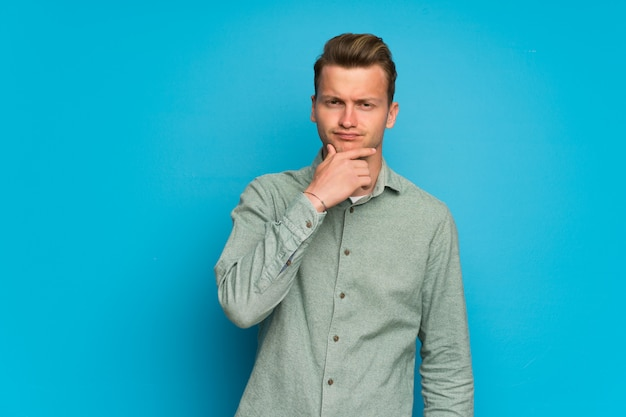 Blonder mann über getrenntem blauem wanddenken Premium Fotos