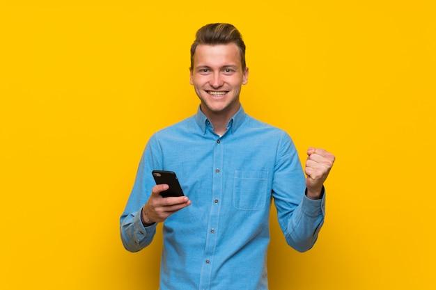 Blonder mann über lokalisierter gelber wand mit telefon in siegposition Premium Fotos
