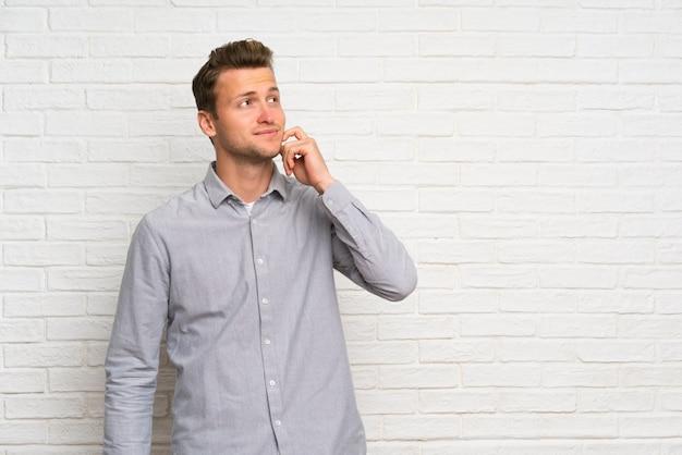 Blonder mann über weißer backsteinmauer eine idee beim oben schauen denkend Premium Fotos