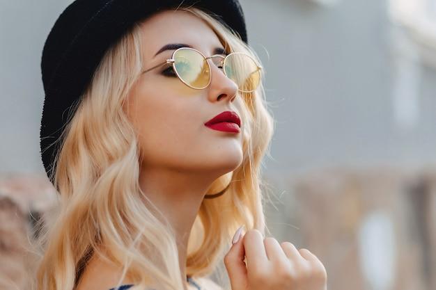 Blondes attraktives mädchen in der sonnenbrille und im stilvollen hut am sommersonnenschein städtisch Premium Fotos