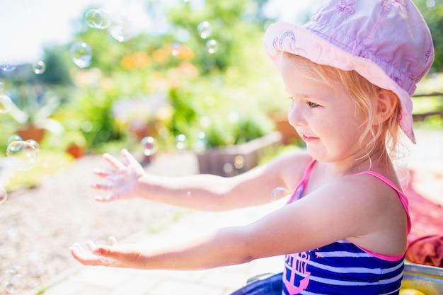 Blondes baby 3 einjahres in einem rosafarbenen hut und in einem blauen entfernten badeanzug, die bad am hinterhof haben und mit luftblasen spielen. Premium Fotos