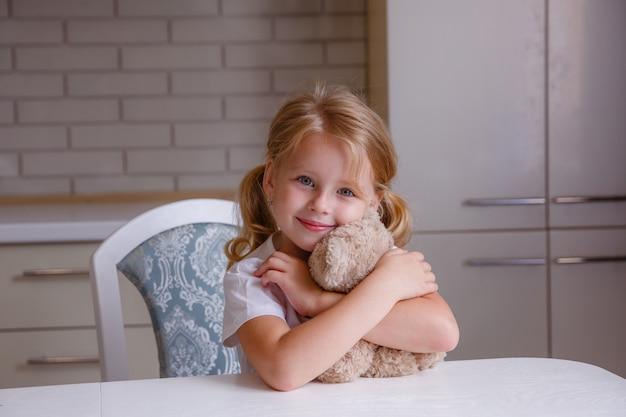 Blondes baby mit bärenspielzeug in der küche vor schlafenszeit Premium Fotos