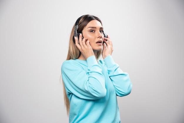 Blondes dj-mädchen hört die musik über kopfhörer und mag es nicht. Kostenlose Fotos