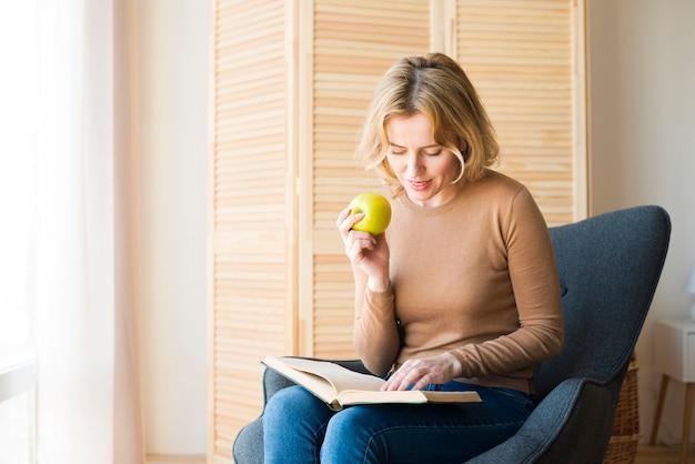 Blondes frauenlesebuch beim essen des apfels Kostenlose Fotos