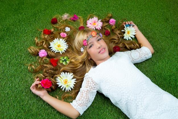 Blondes frühlingsmädchen mit blumen auf haar über gras Premium Fotos