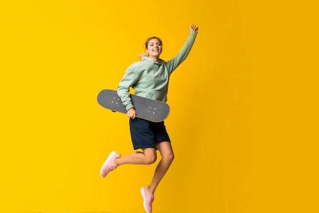 Blondes jugendlichschlittschuhläufermädchen, das über getrenntes gelb springt Premium Fotos