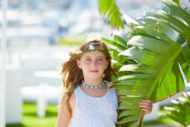 Blondes kindermädchen am bananenbaum verlässt am hellen tag Premium Fotos