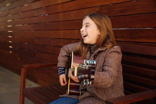 Blondes kindermädchen, das gitarre spielt Premium Fotos