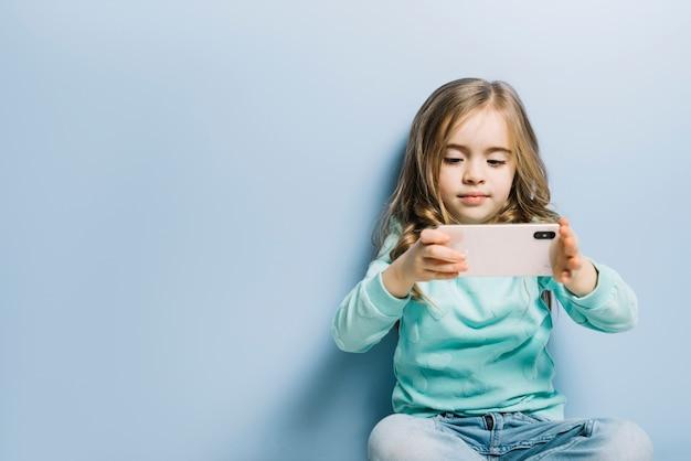 Blondes kleines mädchen, das gegen den blauen hintergrund aufpasst das video am handy sitzt Kostenlose Fotos