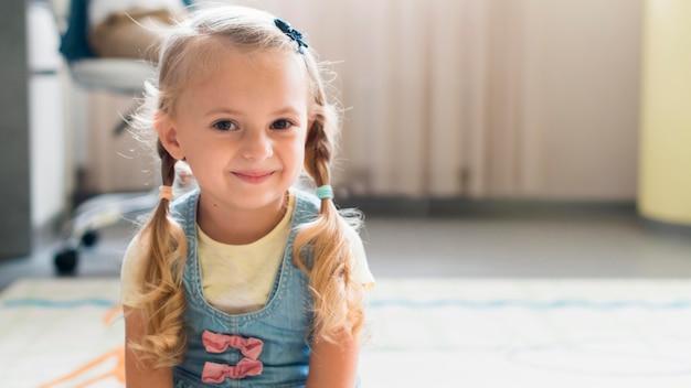 Blondes kleines mädchen, das mit kopienraum lächelt Kostenlose Fotos