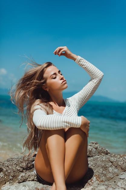 Blondes mädchen auf dem sand am strand sitzen Premium Fotos