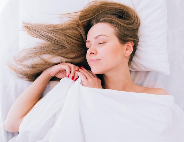 Blondes mädchen, das auf dem bett schläft Kostenlose Fotos