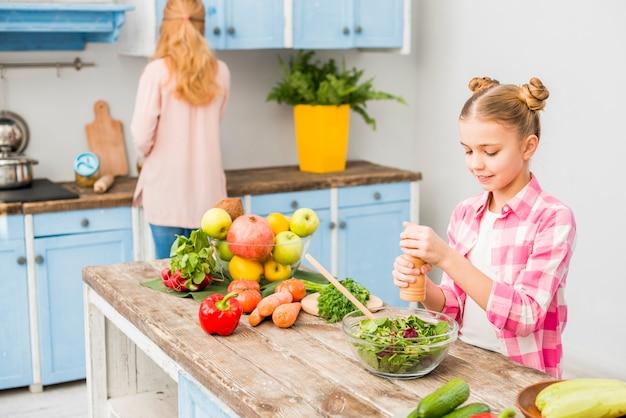 Blondes mädchen, das den pfeffer in der salatschüssel mit ihrer mutter in der küche reibt Kostenlose Fotos