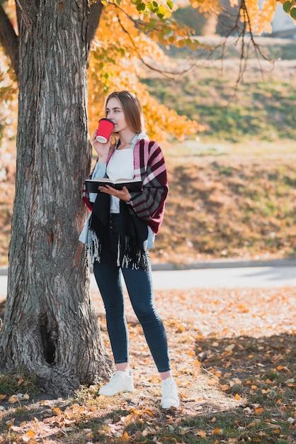Blondes mädchen, das ein notizbuch hält und kaffee trinkt Kostenlose Fotos