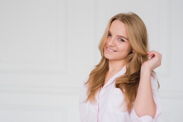 Blondes mädchen, das ihr haar berührt Kostenlose Fotos
