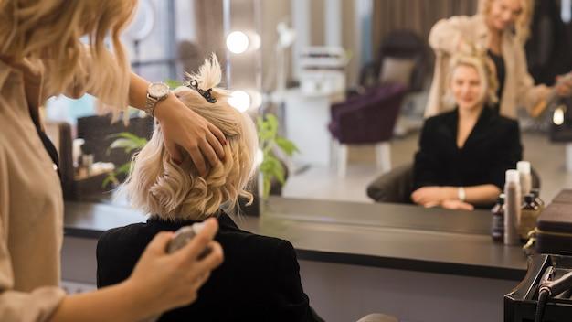 Blondes mädchen, das ihr haar erledigt erhält Kostenlose Fotos