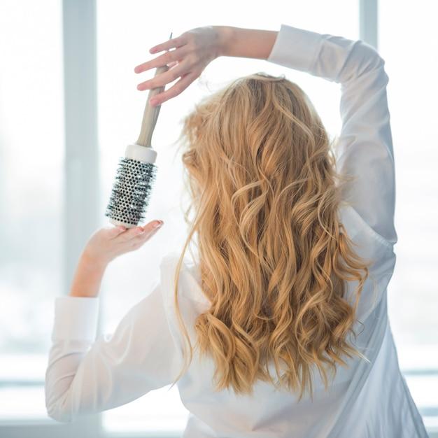 Blondes mädchen, das mit haarbürste aufwirft Kostenlose Fotos