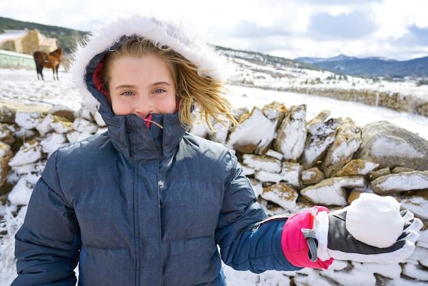 Blondes mädchen, das mit schneeball im winter spielt Premium Fotos