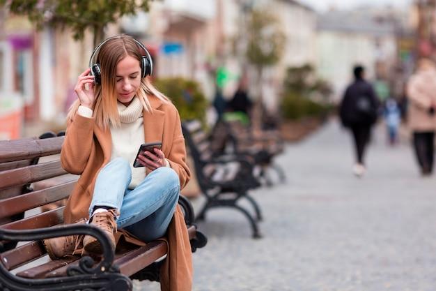 Blondes mädchen, das musik auf kopfhörern mit kopienraum hört Kostenlose Fotos