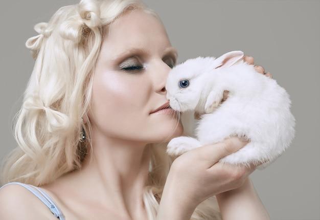 Blondes mädchen des albinos im eleganten kleid, das mit nettem kleinem kaninchen aufwirft Premium Fotos