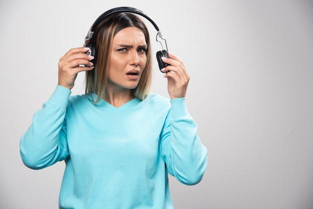 Blondes mädchen im blauen sweatshirt hört die kopfhörer und genießt die musik nicht. Kostenlose Fotos