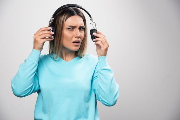 Blondes mädchen im blauen sweatshirt hört die kopfhörer und genießt die musik nicht Kostenlose Fotos