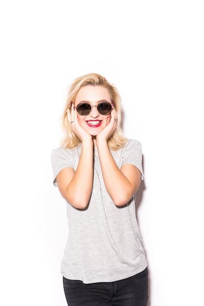 Blondes mädchen im grauen t-shirt hält ihre hände unter ihrem kinn Kostenlose Fotos